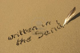12008115-a-feather-used-as-a-quill-pen-to-write-written-in-the-sand